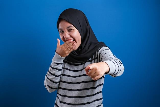 Portret muzułmańskiej dziewczyny w hidżabie śmiejącej się mocno, szczęśliwy wyraz, z bliska strzał głową na niebieskim tle