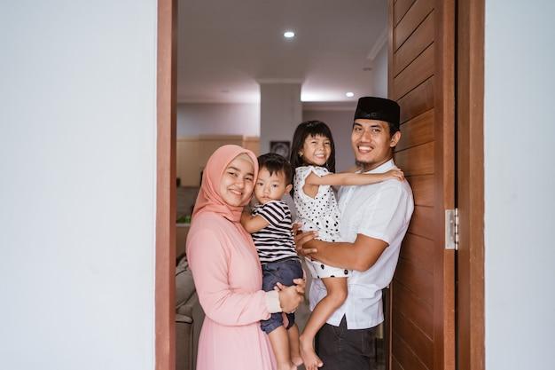 Portret muzułmańskiej rodziny stojącej przed domem przy drzwiach wejściowych, witającej gościa w domu podczas obchodów eid mubarak