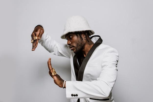 Portret muzyka hip-hopowego. filmowy obraz mężczyzny noszącego białe ubranie i klejnoty