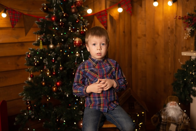 Portret mylić chłopca siedzącego w pobliżu choinki. wesołych świąt i szczęśliwego nowego roku.