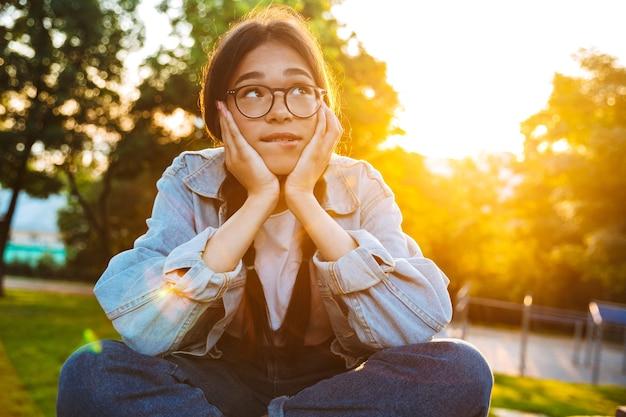Portret myślącej marzącej młodej nastoletniej studentki siedzącej na zewnątrz w pięknym zielonym parku