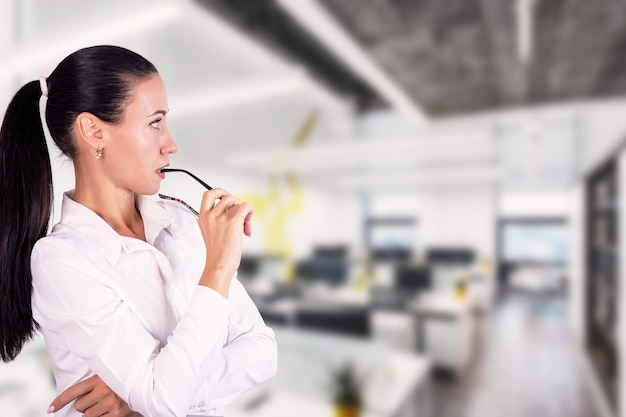 Portret myślącej, młodej pięknej kobiety biznesu w biurze. koncepcja strategii. zdjęcie wysokiej jakości