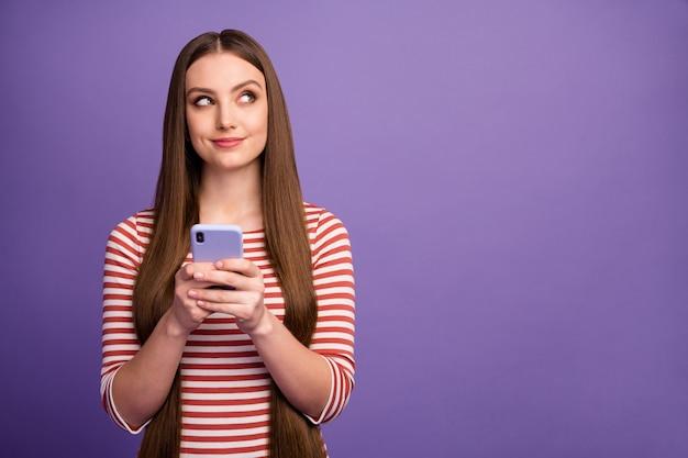 Portret myślącej uroczej słodkiej dziewczyny copyspace użyj smartfona zastanawiam się, czy tematy postów na blogu noszą sweter izolowany na fioletowej ścianie