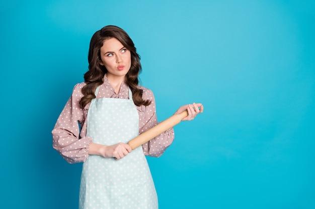 Portret myślącej zamyślonej dziewczyny wyglądają copyspace myśli decydować o tym, jaki smaczny, pyszny przepis piekarnia piec nosić ubrania w kropki na białym tle nad niebieskim kolorem tła