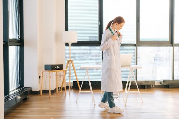 Portret myślenia kobiece lekarz w białym fartuchu stojący na tle okna w słoneczny dzień w gabinecie lekarskim światła.