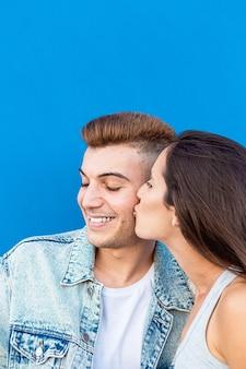 Portret na białym tle młoda para zakochanych całuje na niebiesko