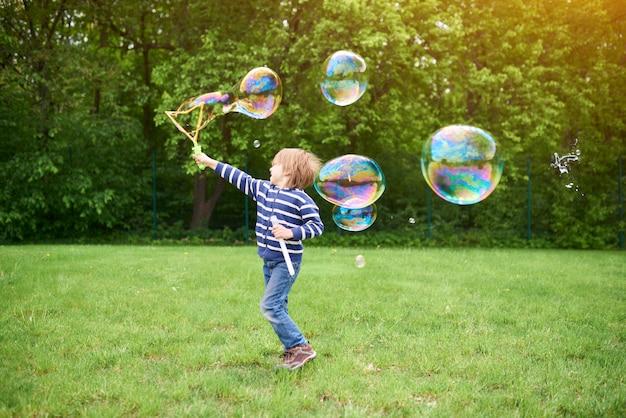 Portret na zewnątrz ładny chłopiec w wieku przedszkolnym dmuchanie baniek mydlanych na zielony trawnik na placu zabaw
