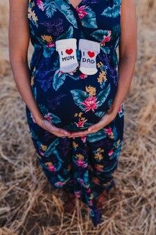 Portret na zewnątrz młodej kobiety w ciąży w żółtym polu. rodzinny styl życia na zewnątrz. trzymanie skarpetek z komunikatem i love mum, i love dad