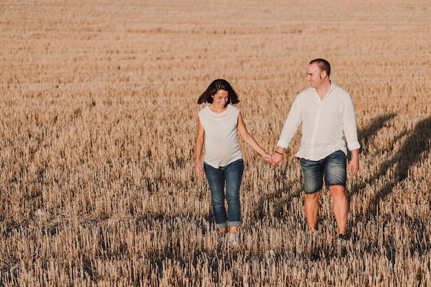 Portret na zewnątrz młodej pary w ciąży, spacery żółtym polu. rodzinny styl życia na świeżym powietrzu.
