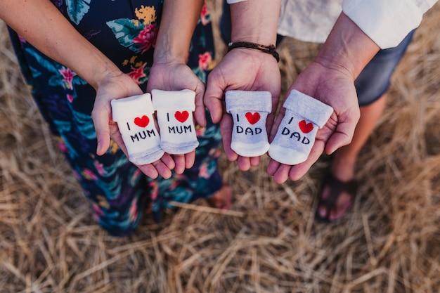 Portret na zewnątrz młodej pary w ciąży w żółtym polu. rodzinny styl życia na zewnątrz. trzymanie skarpetek z komunikatem i love mum, i love dad