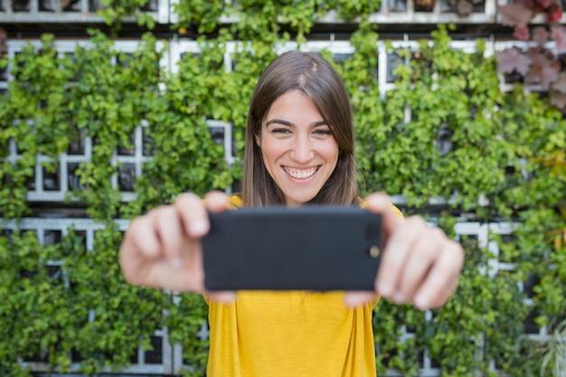 Portret na zewnątrz pięknej młodej kobiety robienie zdjęć z telefonu komórkowego i uśmiechnięty. ubrana w żółtą, swobodną koszulę i uśmiechnięta.