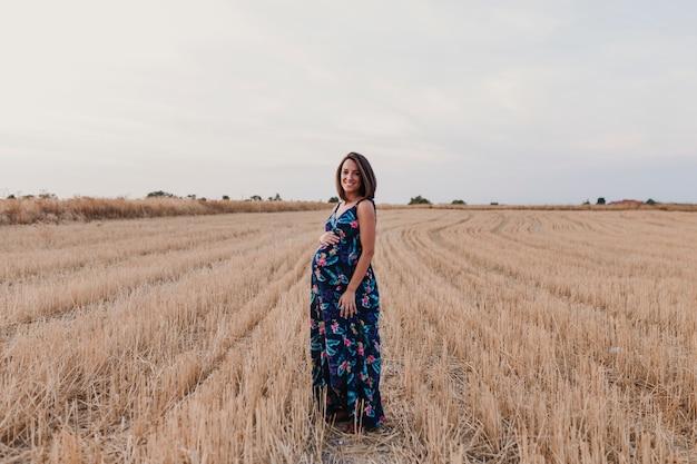 Portret na zewnątrz pięknej młodej kobiety w ciąży w żółtym polu. rodzinny styl życia na świeżym powietrzu.