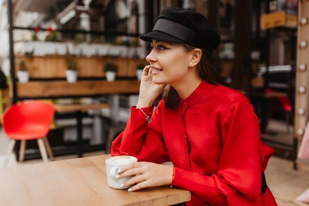 Portret na zewnątrz z profilu modelki z bujnymi rzęsami. ładna dziewczyna pije cappuccino i uśmiecha się nieśmiało