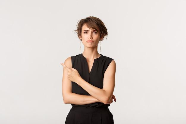 Portret nadąsanej dziewczyny wskazującej na lewy górny róg, narzekającej, stojącej nad bielem.