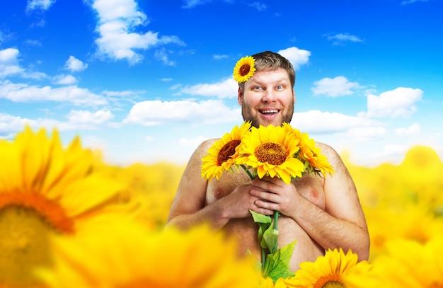 Portret nagiego mężczyzny w polu słonecznika