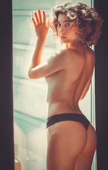 Portret nagiej kobiety blondynka stwarzających w oknie