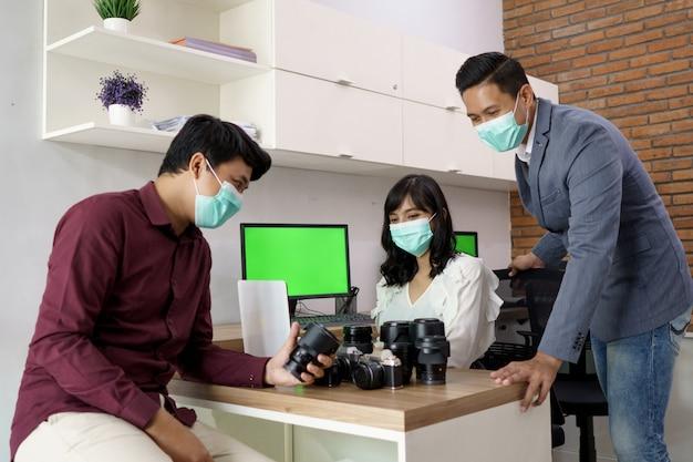 Portret najemcy obiektywu. kto jest wspierany przez obsługę klienta, aby wyjaśnić to przy biurku z maską dla zdrowia