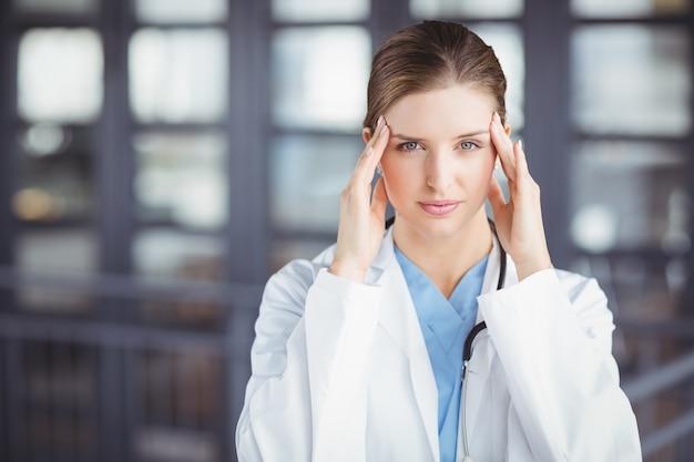 Portret napięta kobiety lekarka z głową w rękach