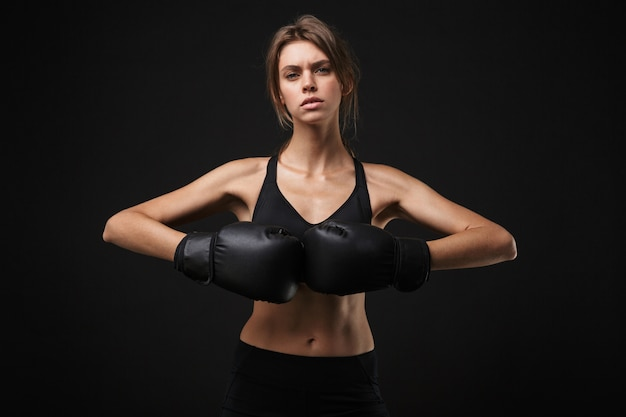 Portret napiętej kaukaski kobieta w sportowej pozowanie przed kamerą z rękawic bokserskich podczas treningu w siłowni na białym tle na czarnym tle