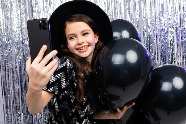 Portret narcystycznego nastolatka na urodziny, biorąc selfie na smartfonie wśród czarnych balonów z helem na błyszczącym tle.