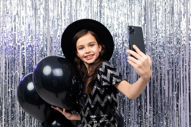 Portret narcystyczny nastolatka na urodziny biorąc selfie na smartfonie wśród czarnych balonów helem na błyszczącym tle