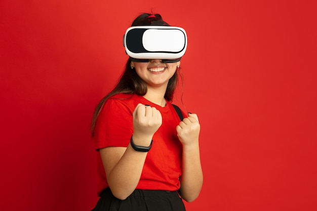 Portret nastolatka azjatyckiego na białym tle na czerwoną przestrzeń. piękna modelka brunetka z długimi włosami w stylu casual