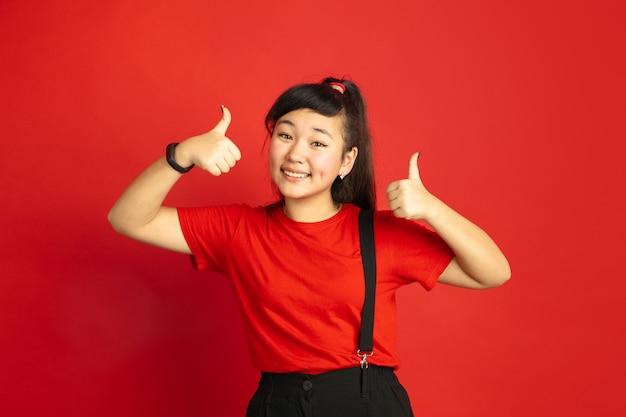 Portret nastolatka azjatyckiego na białym tle na czerwoną przestrzeń