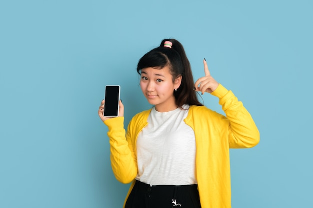 Portret nastolatka azjatyckiego na białym tle na niebieskiej przestrzeni