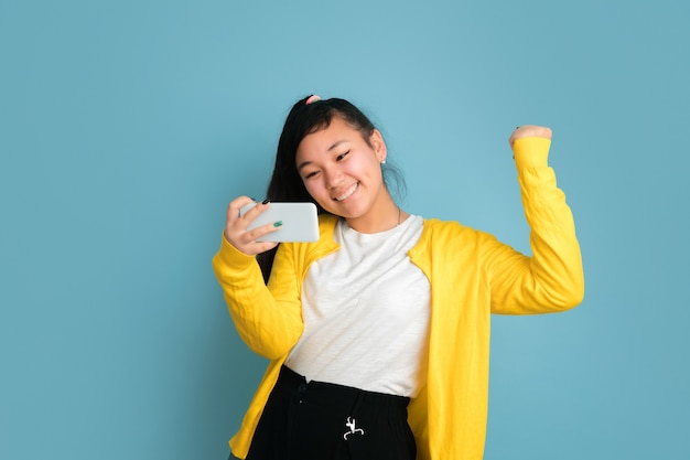 Portret nastolatka azjatyckiego na białym tle na niebieskim tle studio. piękna modelka brunetka z długimi włosami. pojęcie ludzkich emocji, wyraz twarzy, sprzedaż, reklama. korzystanie z telefonu, uśmiechanie się, szczęśliwa wygrana.