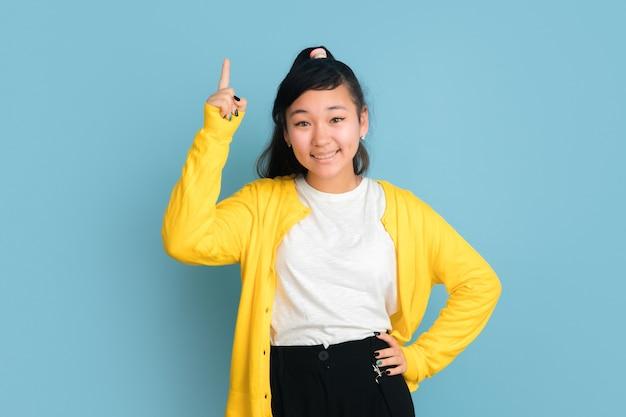Portret nastolatka azjatyckiego na białym tle na niebieskim tle studio. piękna modelka brunetka z długimi włosami. pojęcie ludzkich emocji, wyraz twarzy, sprzedaż, reklama. uśmiechnięty, wskazujący w górę, wygląda uroczo.