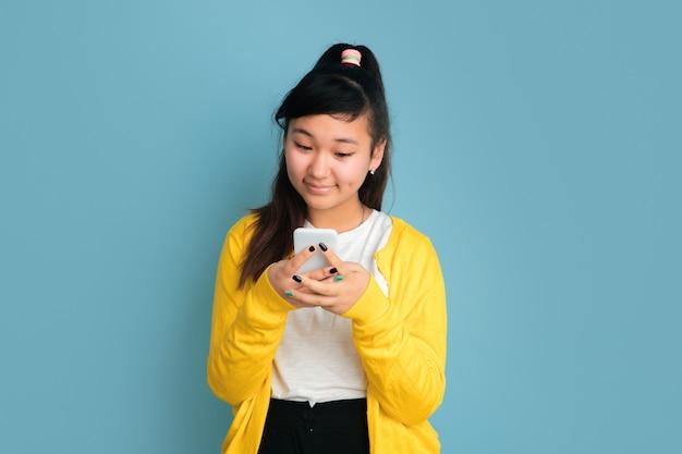 Portret nastolatka azjatyckiego na białym tle na niebieskim tle studio. piękna modelka brunetka z długimi włosami. pojęcie ludzkich emocji, wyraz twarzy, sprzedaż, reklama. używając telefonu, uśmiechając się.