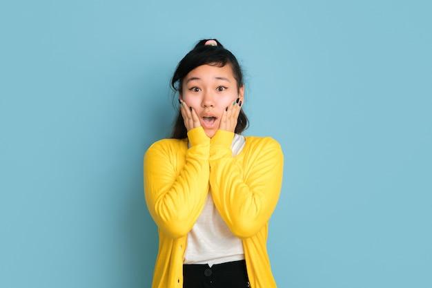 Portret nastolatka azjatyckiego na białym tle na niebieskim tle studio