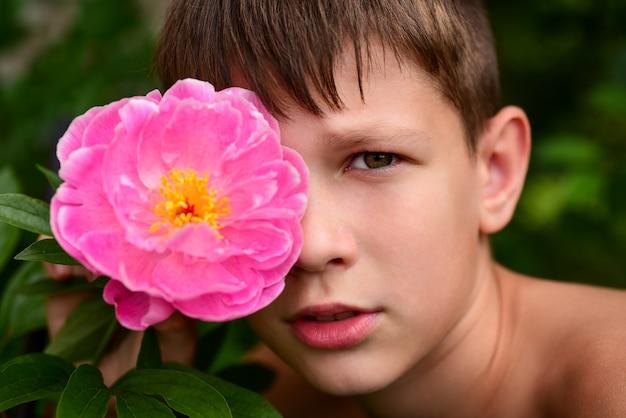 Portret nastolatka chłopca z kwiatem w oku