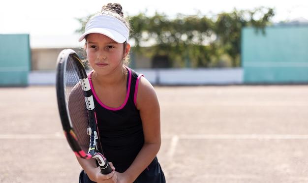 Portret nastolatka, grać w tenisa na boisku sportowym