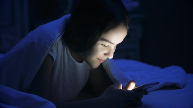 Portret nastolatka leżąc w łóżku i przy użyciu smartfona.