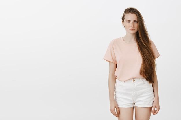Portret nastolatka pozuje na białej ścianie