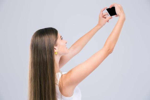 Portret nastolatka robi zdjęcie selfie na smartfonie na białym tle
