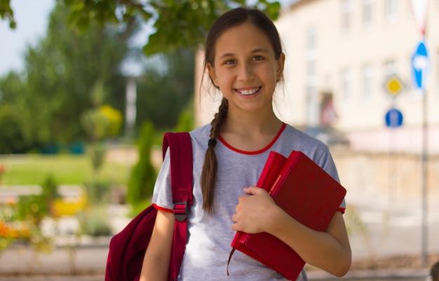 Portret nastolatka stoi przed szkołą trzymając w rękach książki powrót do koncepcji szkoły