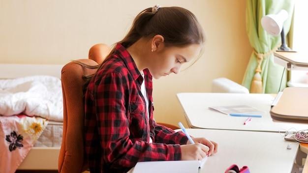 Portret nastolatka studia i odrabiania lekcji w jej sypialni.