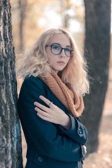 Portret nastolatka w dużych czarnych okularach w jesiennym parku