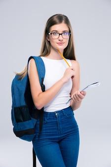 Portret nastolatka z plecakiem trzymającym ołówek i notatnik na białym tle