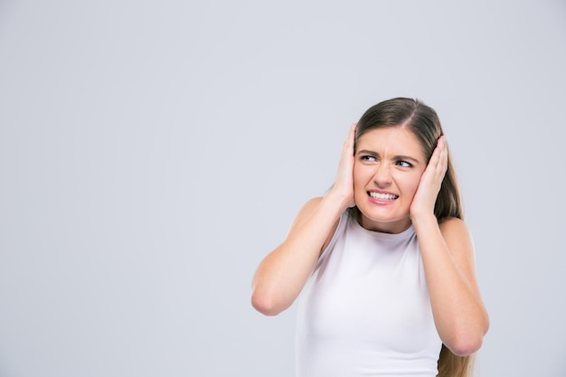 Portret nastolatka zakrywającego jej uszy na białym tle