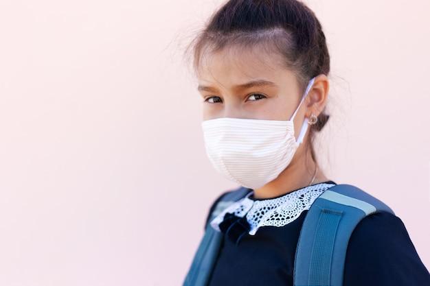 Portret nastolatki po szkole, ubrana w maseczkę medyczną przeciwko koronawirusowi lub covid-19.