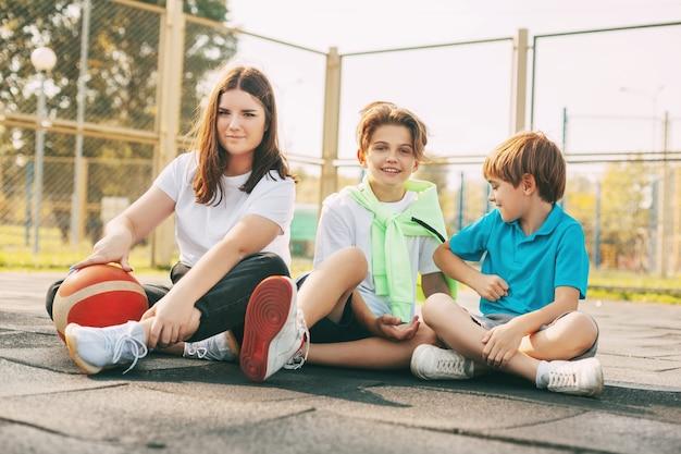 Portret nastolatków siedzi na boisku do koszykówki. dzieci odpoczywają po meczu, rozmawiają i śmieją się