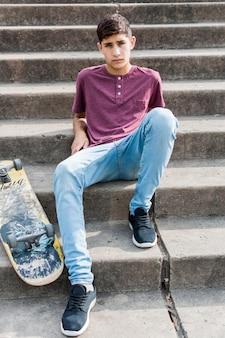 Portret nastoletni chłopak siedzi na betonowym schody z deskorolka