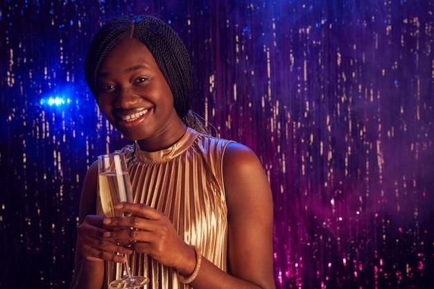 Portret nastoletnich african-american girl gospodarstwa kieliszek do szampana i uśmiecha się do kamery, ciesząc się stroną w nocy balu, kopia przestrzeń