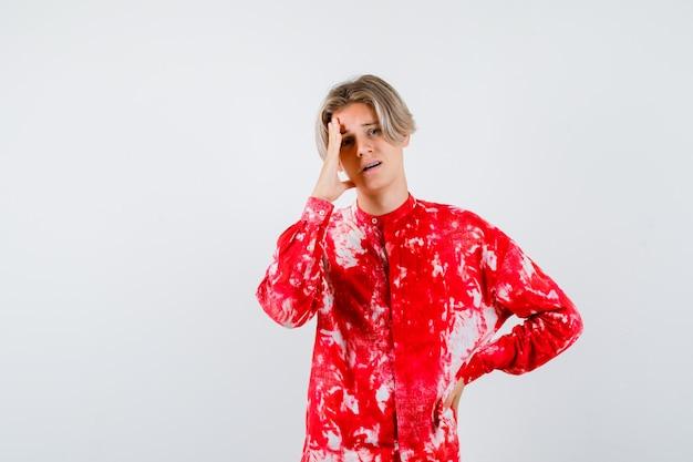 Portret nastoletniego blond mężczyzny z ręką na twarzy w zbyt obszernej koszuli i patrzącym na zamyślony widok z przodu