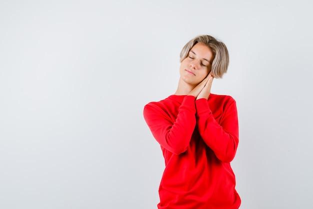 Portret nastoletniego chłopca opierając się na dłoniach jako poduszce w czerwonym swetrze i patrząc sennie z przodu