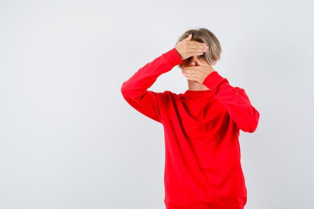 Portret nastoletniego chłopca patrzącego przez ręce w czerwonym swetrze i przestraszonego widoku z przodu