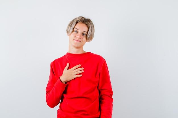 Portret nastoletniego chłopca trzymającego rękę na klatce piersiowej w czerwonym swetrze i wyglądającego na zadowolonego z przodu
